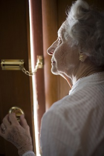Senior Peering out a secured door